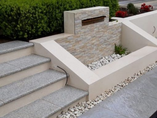 Rock cream porcelain clad water feature and granite steps