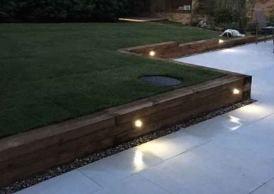 Porcelain patio with sleepers and turf