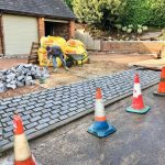 Driveway paving being laid with traffic cones