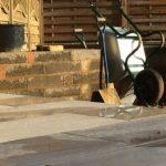 Wheelbarrow and spade propped against engineering blocks