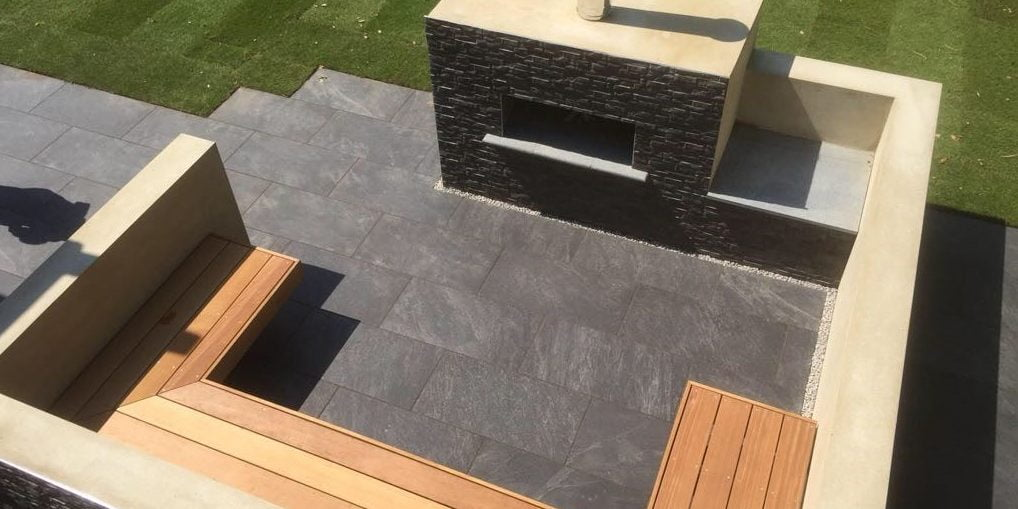Outdoor oven with dark porcelain paving and cladding