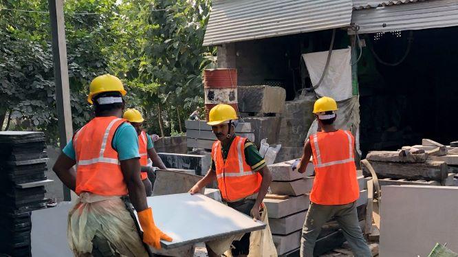 Black granite paving slabs being moved in factory