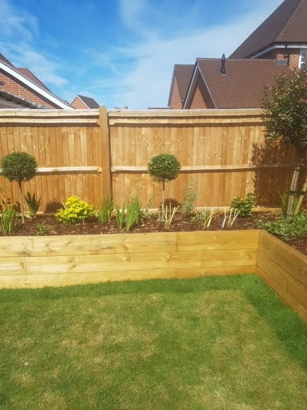 Planed softwood sleeper planters in front of fencing