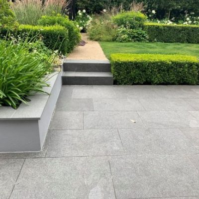 Black granite paving with rendered walls and planting