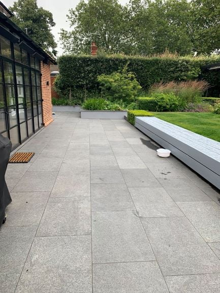 Black granite paved patio with bench seating