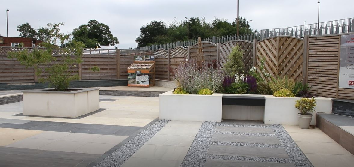 Paving display area with plants and fencing