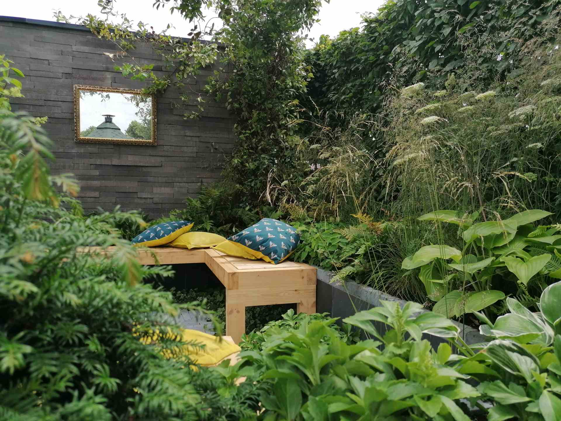 Cosy sunken seating area with lush green planting