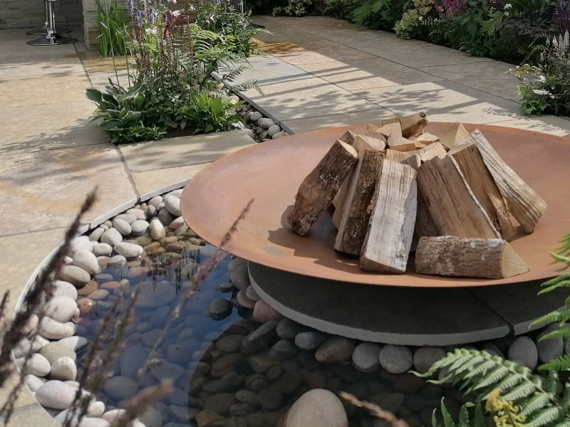 Weathered steel fire pit with water feature and cobble stones