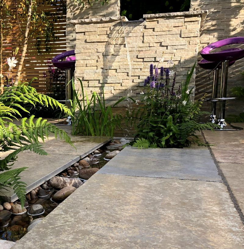 Waterfall and garden rill with stone cobbles and plants